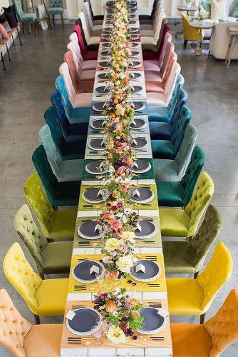 wedding reception decorations in modern style a long table with armchairs of different colors as in a rainbow tableware gray on a table bright flowers studio emp photography