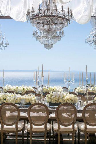 wedding reception decorations near the sea with elegant chandeliers with transparent candlesticks and white roses jessica claire photography