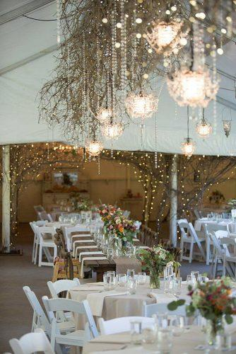 wedding reception decorations rustic tables for guests decorated with flowers room decorated with wooden branches of light bulbs and chandeliers erin johnson photography