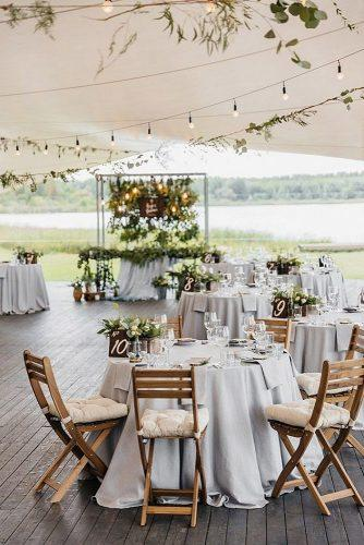 wedding reception decorations rustic tables with white tablecloths and wooden table numbers are decorated with greenery sergey lapkovsky photography