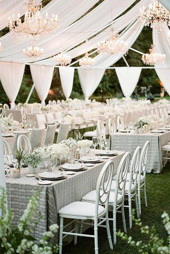 wedding reception decorations white in white under a white awning with golden elegant chandeliers and unusual chairs a savvy event via instagram