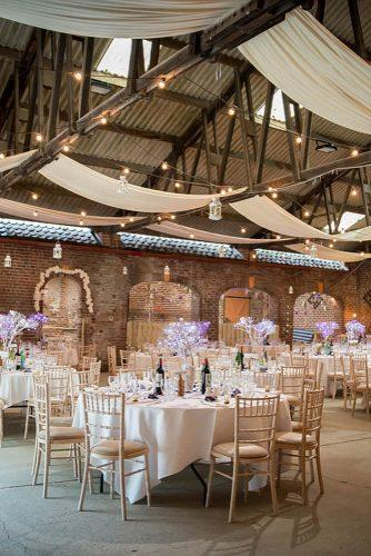 wedding reception decorations with round tables white white tablecloths and luminous trees on them under the ceiling of the lamp lights and white cloth jenny maden photography
