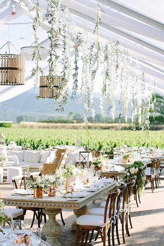 wedding reception decorations with stone tables golden vases and candlesticks from the ceiling descends greens and modern chandeliers a savvy event via instagram