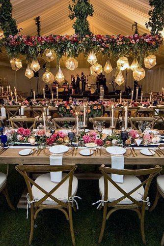 wedding reception decorations with wooden tables with candles geometrical lamps and pink flowers paul barnett photographer
