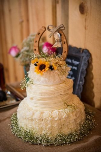 fall wedding cakes rustic white buttercream with baby breath and sunflowers with horseshoe on top tanna white photography