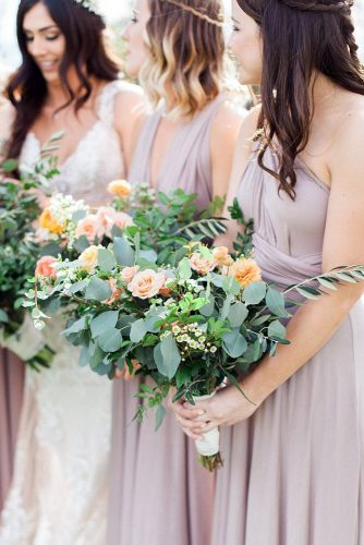 green wedding florals a lot of greenery and pink yellow flowers in the hands of bridesmaids kelsie pinkerton via instagram