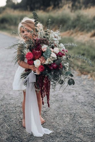green wedding florals in the hands of a girl in a white lush bouquet with claret flowers and greens kat grabowski via instagram