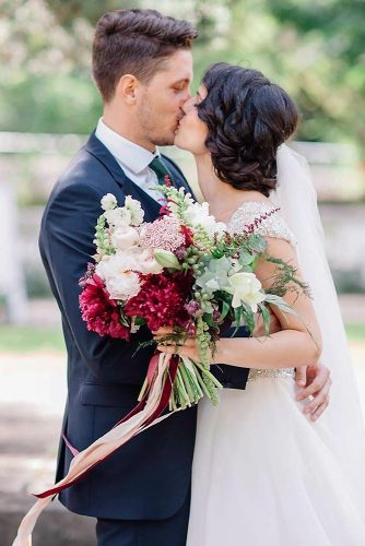 green wedding florals with white and burgundy flowers decorated with ribbons deers photography via instagram