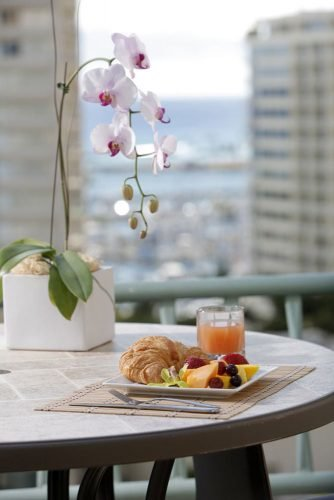 hawaii honeymoon breakfast with croissant and fruit on the hotel balcony ramadaplazawaikiki