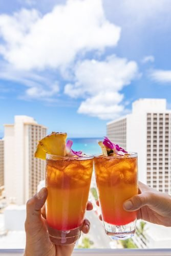 hawaii honeymoon clink glasses on the hotel balcony hyattplacewaikiki