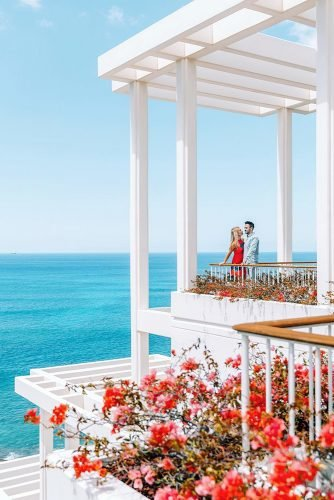 hawaii honeymoon couple on a white veranda decorated with red flowers lifeandmylens