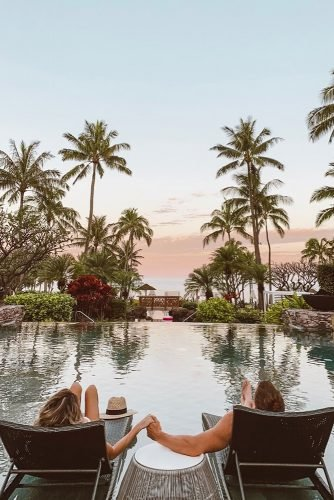 hawaii honeymoon couple on the loungers by the pool hellofashionblog