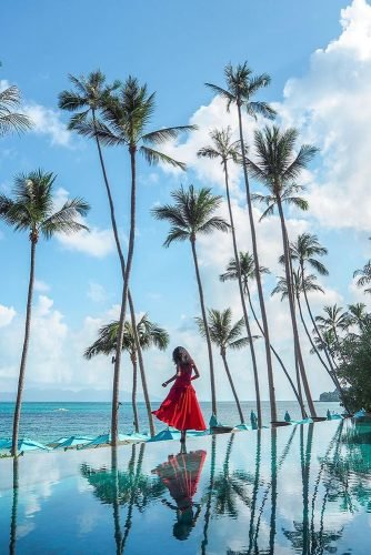 hawaii honeymoon girl in a red dress high palms the sky is reflected in the water thejoergensen