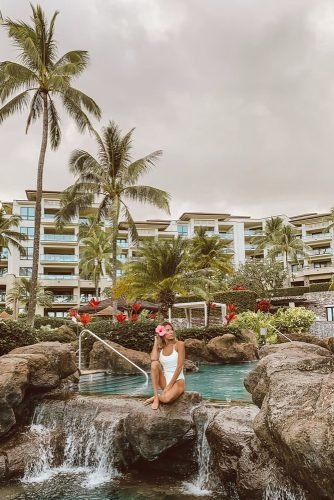 hawaii honeymoon girl in a white bathing suit with a flower in her hair by the pool hellofashionblog
