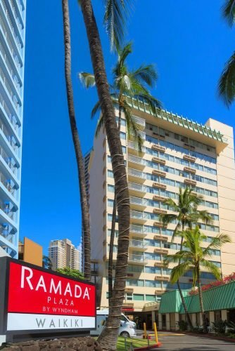 hawaii honeymoon sign at the entrance to the hotel tall building among palm trees ramadaplazawaikiki