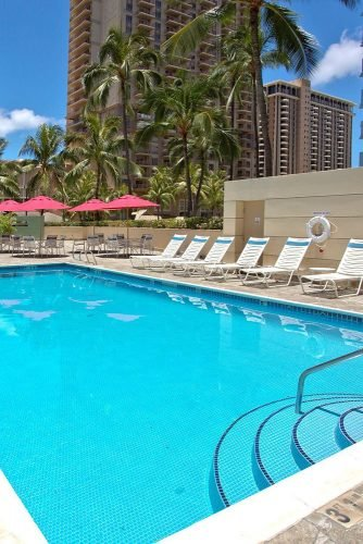 hawaii honeymoon swimming pool with sun loungers in the courtyard ramadaplazawaikiki