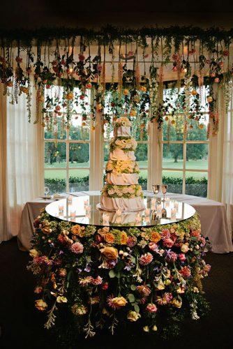 mirror wedding ideas white bridal cake on mirror stand with flowers kristyn hogan photography