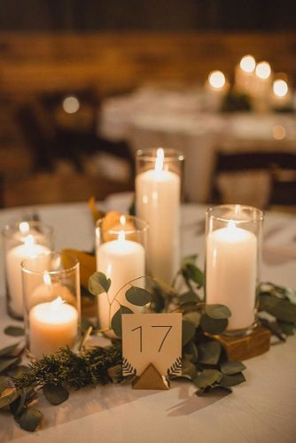 non floral wedding centerpieces candles in glass candlesticks with greenery jophoto