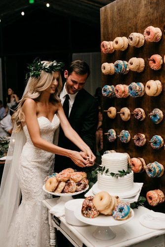 wedding dessert table ideas the groom and the bride cut the cake around the plate with donuts and on the wall donuts luke and mallory via instagram