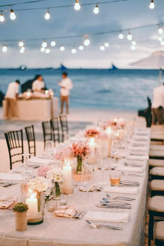 wedding light reception decorated with garlands with lamps on tables candles and bouquets owen and nikka wedding photography