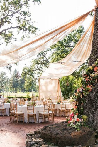 wedding tent light pink cloth as an awning is mounted on a tree decorated with flowers on tables flowers and golden candlesticks quintana events via instagram