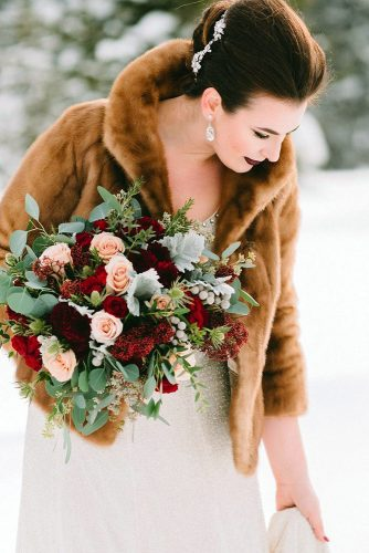 winter wedding bouquets in the hands of the bride a bouquet with greens tender roses and burgundy flowers darren roberts via instagram