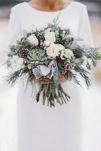 winter wedding bouquets with white roses succulents and pine cones jocelyn's floral via instagram