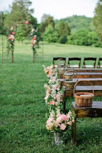 country wedding aisle decorated with flowers and wicker baskets kristyn hogan photography