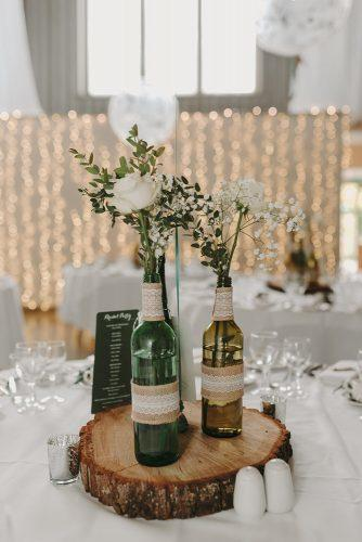 country wedding flowers in grass bottles with burlap and lace kelsie low photography