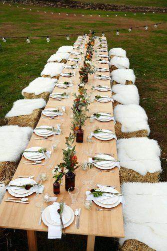 country wedding long table decorated with flowers and hay bale seatings eyeswoon via instagram