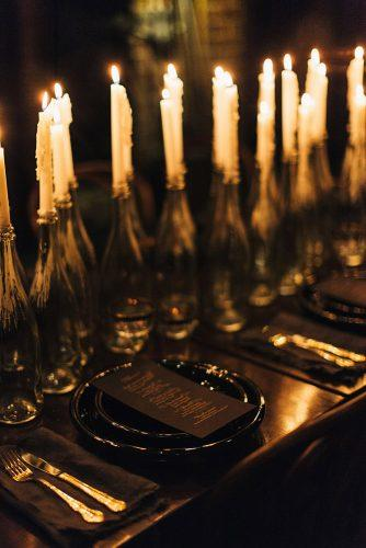 halloween wedding ideas black dishes on bridal table with a lot of candles in bottles the_lane