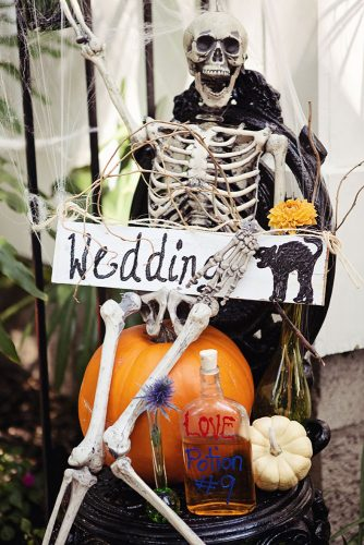 halloween wedding ideas on a pumpkin sits a skeleton in a spiderweb with an inscription wedding april smith & co photography