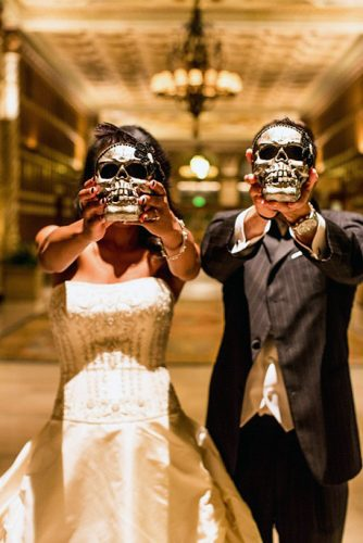 halloween wedding ideas photo the bride and groom cover their faces with their skulls beautifuldayphotography
