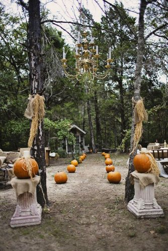 halloween wedding ideas wedding pass of orange pumpkins with a massive golden chandelier with candles rachael lindsy photography
