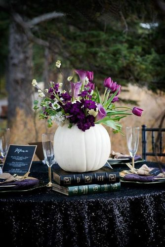 halloween wedding ideas white vase in the form of a pumpkin with purple flowers tulips and callas on a table covered in black christydswanbergphotography