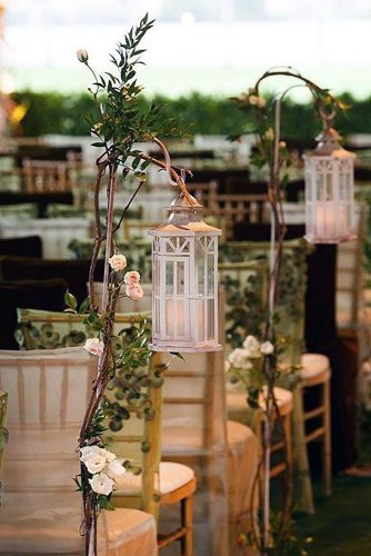 lantern wedding centerpiece aisle decorated with white lanterns suspended on wooden branches with flowers muse books via instagram