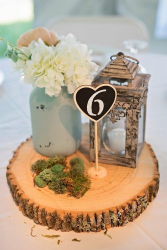 lantern wedding centerpiece on a wooden piece of lantern flowers in a jar of moss and a table number bentley photography via instagram