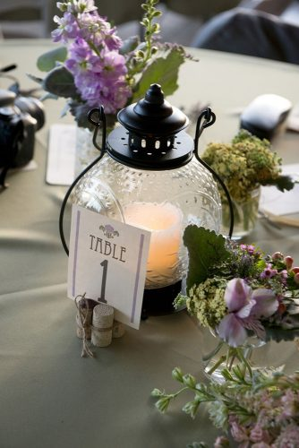 lantern wedding centerpiece round lantern with a candle and a table number surrounded by flowers brent gulledge photography