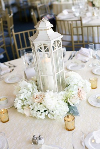 lantern wedding centerpiece white wooden lantern with a candle surrounded by white flowers and ruddy roses on the wedding table millimeter photo via instagram
