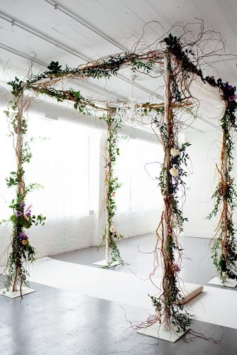 loft decorating ideas in a snow white loft a voluminous arch decorated with branches of greens and flowers olivia leigh photographie