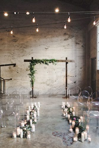 loft decorating ideas in the industrial style wooden arch decorated with greenery passage in candles chairs for guests transparent meghan elise photography
