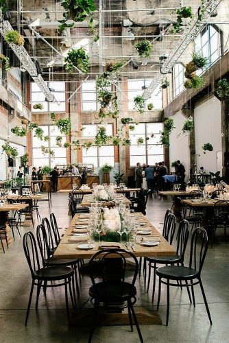 loft decorating ideas large space wooden table black chairs on the table greenery and candles under the ceiling decoration with greenery and transparent balls jenn emerling via instagram