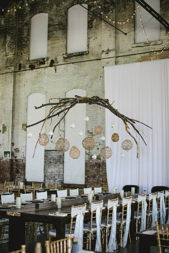 loft decorating ideas reception in rustic style with elegant elements over the table decoration of wooden sticks and golden balls with lights aimee jobe photography