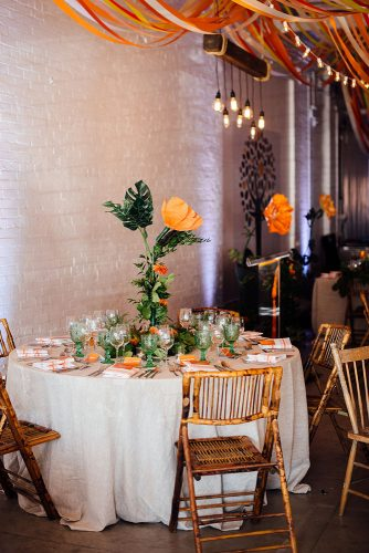 loft decorating ideas reception with bright colors on the tables and orange tapes under the ceiling and light bulbs sara monika via instagram