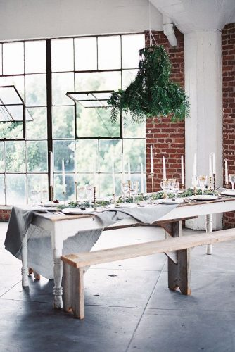 loft decorating ideas wooden table with candles and greenery benches in the loft with large windows wedding photographer via instagram