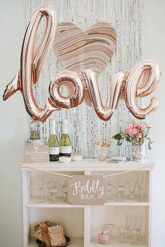 rose gold wedding decor a bar with champagne is decorated with balloons with an inscription love is an adventure via instagram