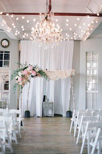 rose gold wedding decor arch on birch sticks with a pink cloth and flowers above the aisle golden lights brklyn view photography