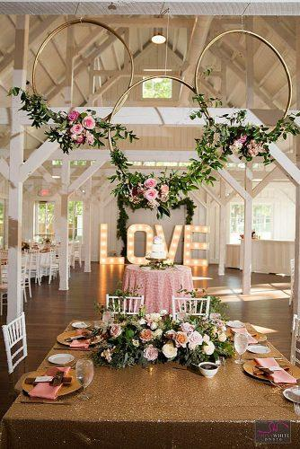 rose gold wedding decor over a table with a golden tablecloth gold hoops with pink roses simply white photo