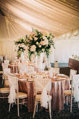 rose gold wedding decor table laid with a beautiful tablecloth with flowers in a high vase under the tent with lights lawson photography