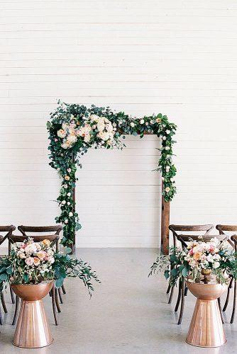 rose gold wedding decor wooden arch decorated with flowers golden vases with flowers in the aisle emilie anne photography